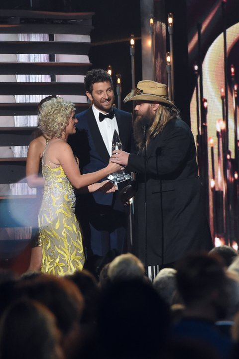 NASHVILLE, TN - NOVEMBER 04: Singers Brett Eldredge (L) and Cam (2nd L) present Chris Stapleton with New Artist of the Year award onstage at the 49th annual CMA Awards at the Bridgestone Arena on November 4, 2015 in Nashville, Tennessee. (Photo by Terry Wyatt/WireImage)
