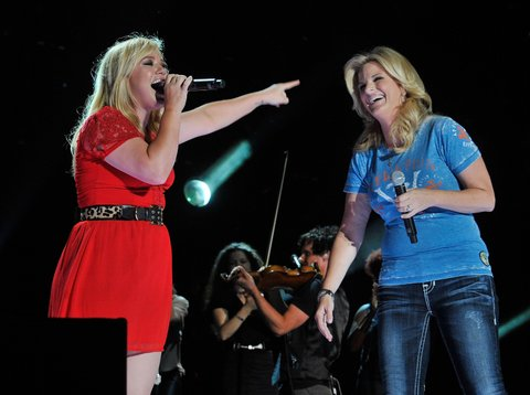 NASHVILLE, TN - JUNE 08: Kelly Clarkson and Trisha Yearwood point at each other after a performance at LP Field during the 2013 CMA Music Festival on June 8, 2013 in Nashville, Tennessee. (Photo by Frederick Breedon IV/WireImage)