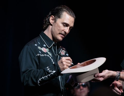 Matthew McConaughey signs Jack Ingram's cowboy hat before it is thrown into the audiance during the 5th annual Mack, Jack & McConaughey Gala at ACL Live on April 20, 2017 in Austin, Texas. The non-profit group raises money for youth organizations. / AFP PHOTO / SUZANNE CORDEIRO        (Photo credit should read SUZANNE CORDEIRO/AFP/Getty Images)