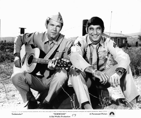 Glen Campbell with a guitar sitting with Joe Namath, both wearing military uniforms in a scene from the film 'Norwood', 1969. (Photo by Paramount Pictures/Getty Images)