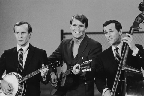 circa 1965:  American folk singer Glen Campbell (C) performs with American comedy duo, the Smothers Brothers (Tom (L) and Dick Smothers) on their television show, 'The Smothers Brothers Comedy Hour.' Campbell plays twelve-string guitar, Tom plays banjo, and Dick plays standup bass.  (Photo by Hulton Archive/Getty Images)