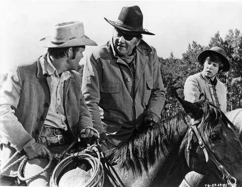1969:  John Wayne, in his Oscar winning performance as Rooster Cogburn, in scene with Kim Darby and Glen Campbell from the movie 'True Grit' directed by Henry Hathaway in 1969.  (Photo by Michael Ochs Archives/Getty Images)