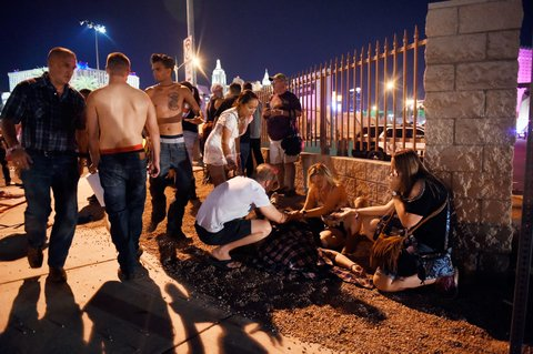 LAS VEGAS, NV - OCTOBER 01:  People tend to the wounded outside the Route 91 Harvest Country music festival grounds after an apparent shooting on October 1, 2017 in Las Vegas, Nevada.  There are reports of an active shooter around the Mandalay Bay Resort and Casino.  (Photo by David Becker/Getty Images)
