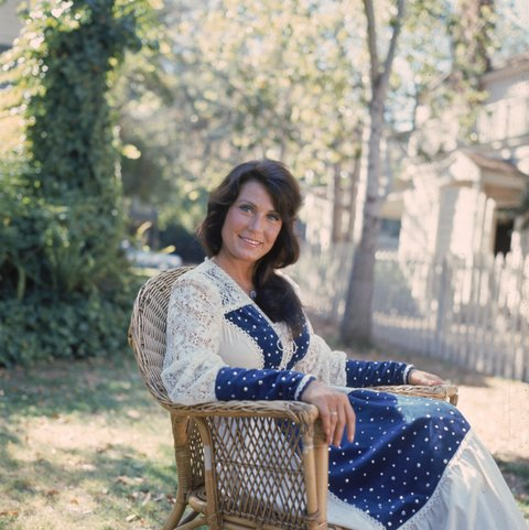 1978, Portrait of American country music singer and musician Loretta Lynn sitting outdoors in a lace dress. (Photo by Getty Images/Getty Images)