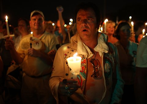 MEMPHIS, TN - AUGUST 15:  Elvis Presley impersonator, Mark Omdahl from Conway, North Dakota holds a candle during a vigil outside the front gates of Graceland Mansion, the home of Elvis Presley, on August 15, 2007 in Memphis, Tennessee. This week marks the 30th Anniversary of the death of the Rock and Roll legend.  (Photo by Joe Raedle/Getty Images)