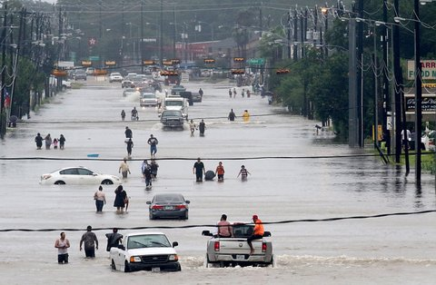 TOPSHOT - People walk through the flooded waters of Telephone Rd. in Houston on August 27, 2017 as the US fourth city city battles with tropical storm Harvey and resulting floods. / AFP PHOTO / Thomas B. Shea        (Photo credit should read THOMAS B. SHEA/AFP/Getty Images)