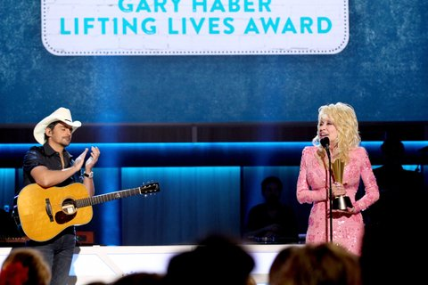 NASHVILLE, TN - AUGUST 23:  Brad Paisley (L) presents Dolly Parton with the Gary Haber Lifting Lives Award onstage during the 11th Annual ACM Honors at the Ryman Auditorium on August 23, 2017 in Nashville, Tennessee.  (Photo by Terry Wyatt/Getty Images for ACM)